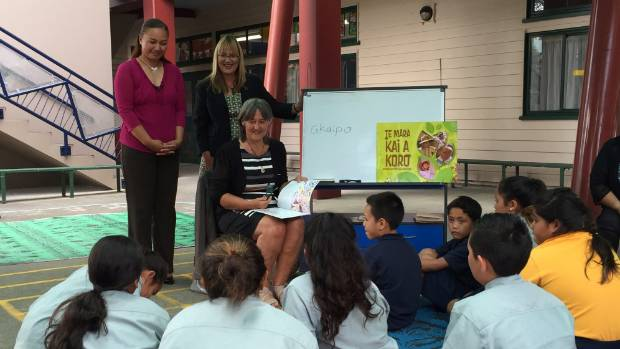 Green MP Catherine Delahunty reads a te reo book to students. Surrounded by MPs Marama Davidson and Denise Roche.