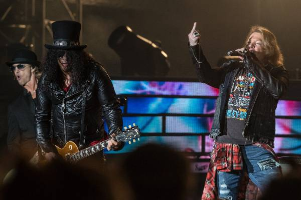 Guns N' Roses lead singer Axl Rose, lead guitarist Slash, and bassist Duff McKagan (far left) rock the crowd.