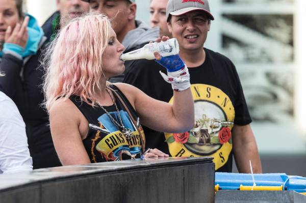 A thirsty fan finishes her refreshment before heading inside the stadium.