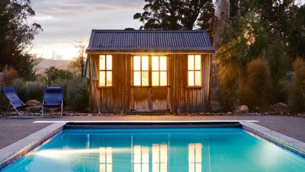 A little pool house provides a focal point at night and a handy spot to get changed or stash pool paraphernalia.