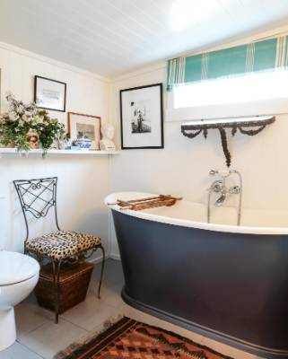 An old black and white photograph hanging above the beloved slipper bath came from a Turnbull Library sale and depicts a ...