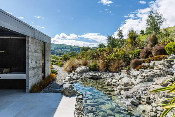 The water feature ends in a natural-looking pool to the south of the house alongside a barbecue and outdoor dining area.