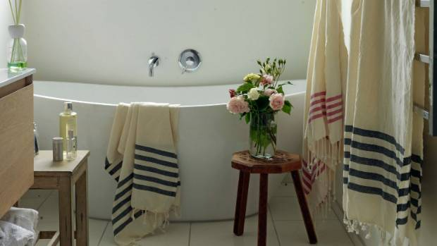 Striped blanket towels cover this modern flower-fiilled bathroom in Nelson.