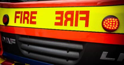Fire crews are working to free two people trapped after a van collided with a truck in Parakai.