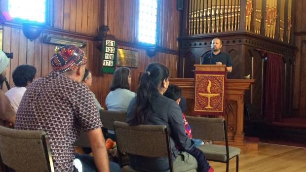 Unite advocate Joe Carolan defends the students' right to stay in New Zealand from the pulpit of Ponsonby's Unitarian church.