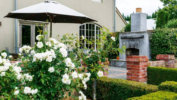 'Iceberg' and standard 'Windrush' roses add to the English feel of the terrace; the fireplace makes it a year-round ...