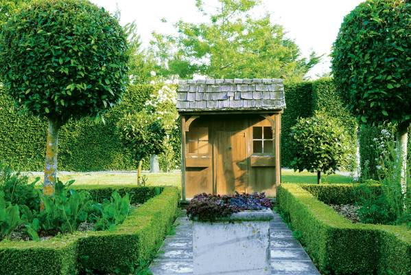 Harriet's playhouse is the focal point of a herb garden edged with Buxus sempervirens 'Suffruticosa' and featuring ...
