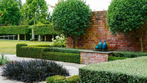 A walled pond, flanked by olive trees, screens the front terrace while buxus, black ophiopogon and corokia soften the ...