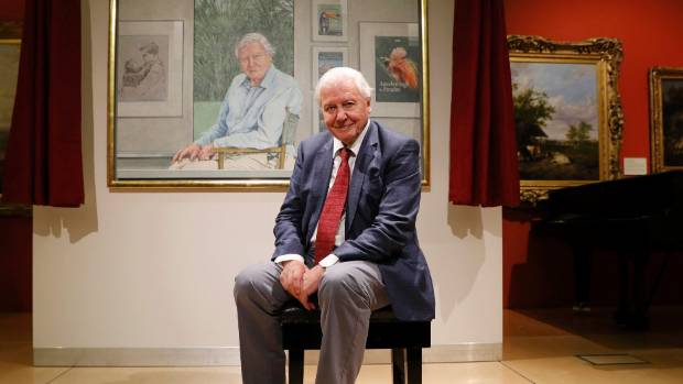 David Attenborough poses next to a portrait of himself in Leicester, Britain, by Bryan Organ to mark his 90th birthday ...