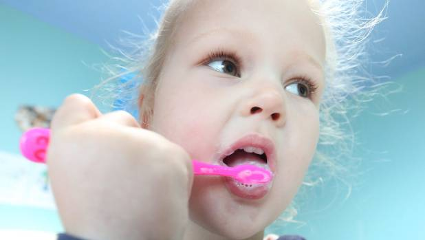 Kayla Flood, 3, earns a gold star by brushing her teeth.