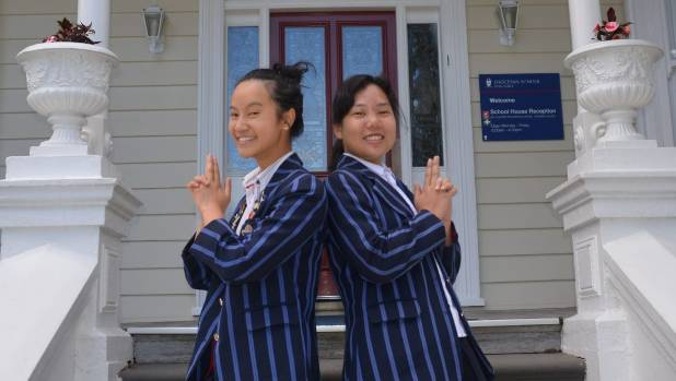 Joanna Li and Nicola Chang are having fun celebrating their academic success.