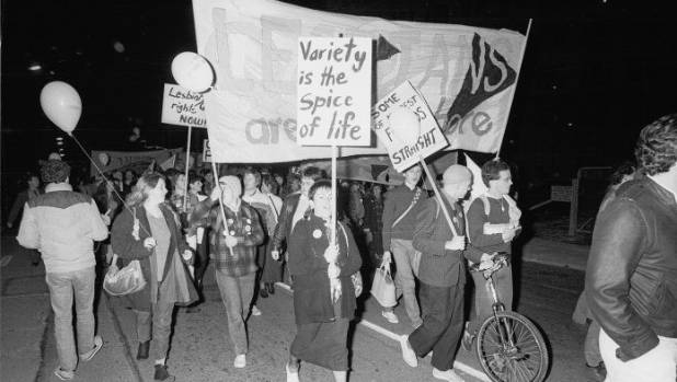 Placard and banner carrying demonstrators in a march in support of homosexual law reform in May of 1985.