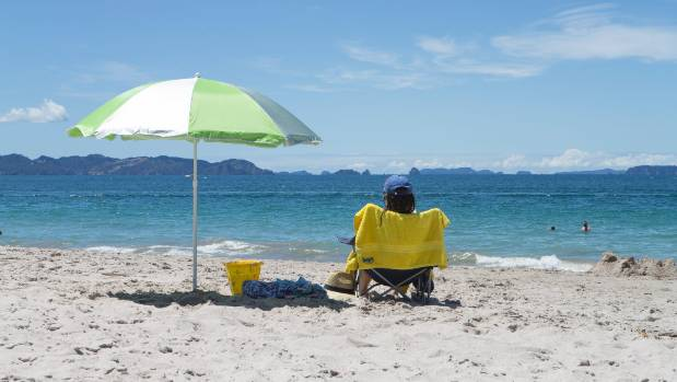 DECEMBER 30: On the left, a sun umbrella. On the right, a sunbather. Up above Hahei Beach in Coromandel, a scorching sun.