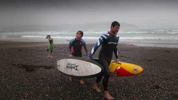 JANUARY 4: Steven Kilduff with his surfer kids Sam, 11 and Paige, 13 struggle out of the water as a mid-afternoon squall ...