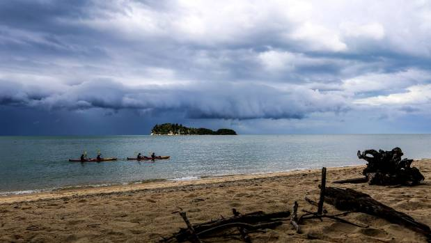 JANUARY 6: Kayakers paddle past Apple Tree Bay in the Abel Tasman National Park with a storm looming in the background.