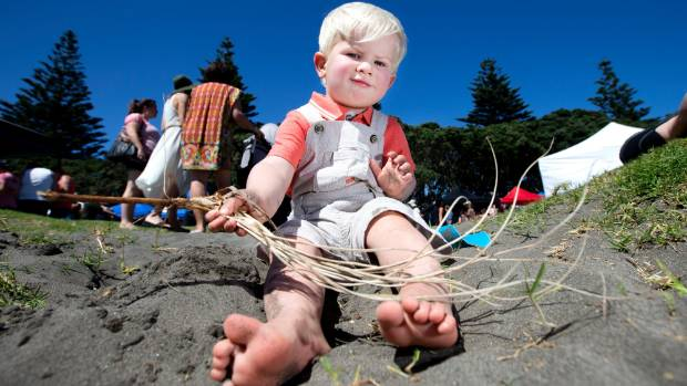 FEBRUARY 5: Harris Bowman, 2, dips his feet in the sand while visiting the seaside markets at Taranaki's Ngamotu Beach.