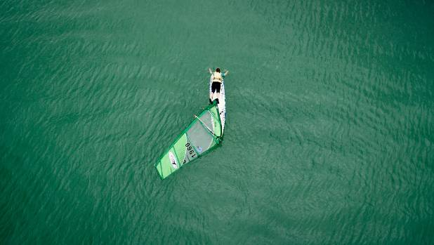 DECEMBER 26: At Maraetai Beach in Auckland, a wind surfer paddles his board back to shore after the wind fell away - and ...