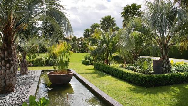 This water feature near the house's entrance canopy has jelly palms (Butia capitata) to its left and, to the right, ...