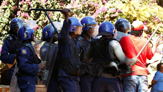 Police officers clash with political protesters during a protest in Harare, the capital of Zimbabwe.