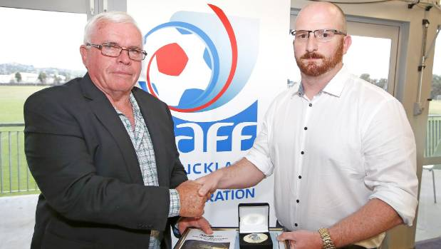 Ants Owens, right, from Metro FC receives a long service award from the Auckland Football Federation's John McLeod.
