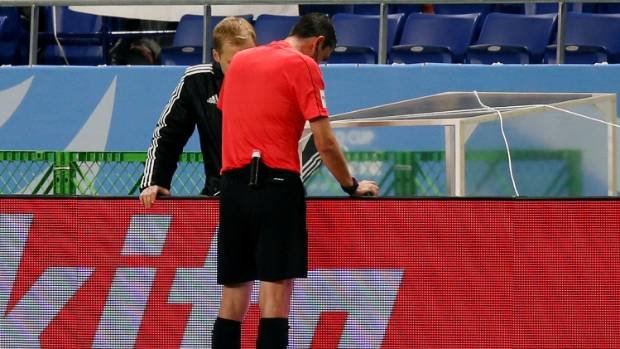 Referee Viktor Kassai views a video replay before his decision to award a penalty in the match between Atletico Nacional ...