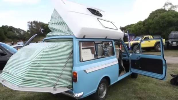 Little 1971 Bedford camper among classic cars and hot rods at