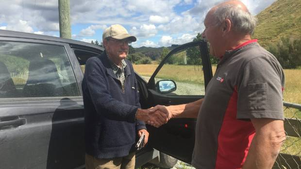 Rural postie Ron Lawrence shakes hands with Ian Munn on Lawrence's last day.