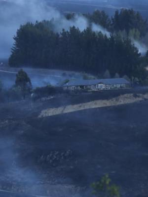 A shed burns as the fire continues to travel across the Port Hills.