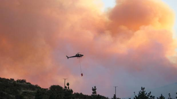 A helicopter battles fires on the Port Hills.