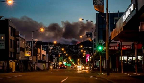 Smoke from the Port Hills blaze forms a dark backdrop to Christchurch's Colombo St.