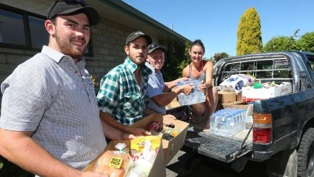 Tyler Fifield, second from left, helps package supplies for earthquake-affected farmers with friends, from left, Josh ...
