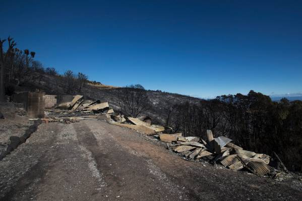 Blackened earth and the remains of buildings are all that is left after huge fires on Christchurch's Port Hills.
