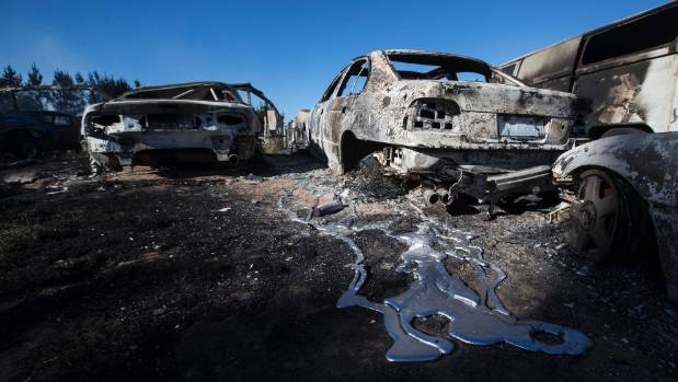 Melted metal pools beneath the burned out remains of a car. Christchurch fireman Omar Yusaf helped rescue the Gordon ...