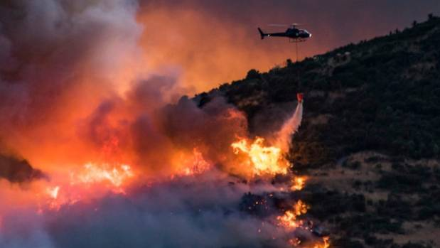A helicopter douses flames on the Port Hills on Monday night.