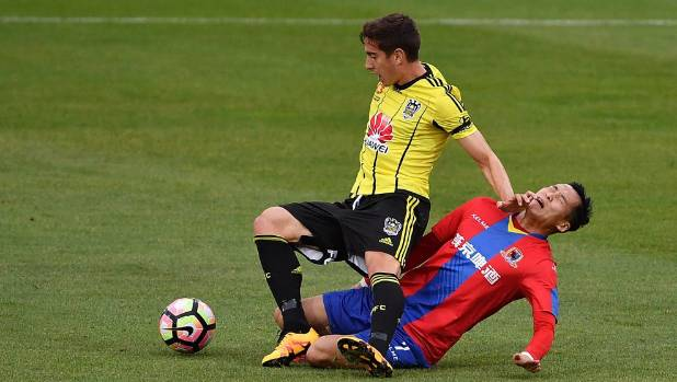 Alex Rodriguez of the Wellington Phoenix and Jin Hui of Beijing BG clash at Westpac Stadium on Tuesday.