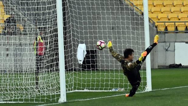 Beijing BG goalkeeper Liu Tianxin is beaten by a penalty from Wellington Phoenix's Kosta Barbarouses.