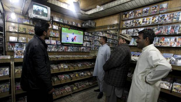 A group of men watch a Pakistan Super League (PSL) cricket match between Islamabad United and Peshawar Zalmi on TV sets ...