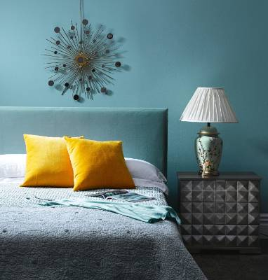 Velvet yellow cushions and a blue velvet headboard give this bedroom a luxurious look.