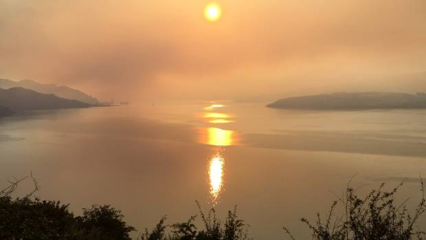 Thick smoke from the spreading Port Hills fire envelopes Lyttelton Harbour on Wednesday morning.