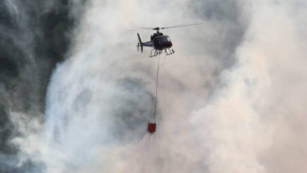 Helicopters with monsoon buckets fight the fires on Christchurch's Port Hills.