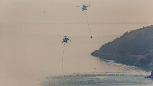 Helicopters fill monsoon buckets from Lyttelton Harbour on Wednesday.