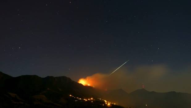 What looks like a meteor streaks by as flames engulf the top of Christchurch's Port Hills.