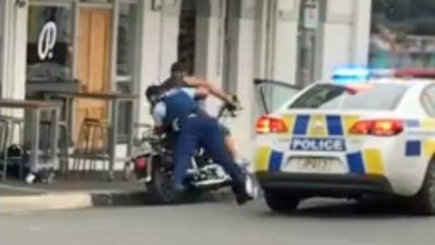 A bartender captured the moment a man was tackled off his motorbike by a police officer outside a Kingsland bar.