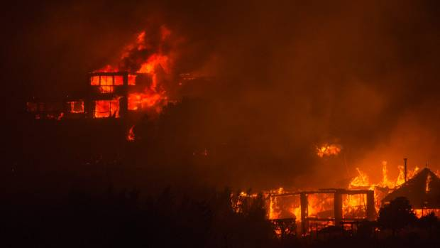 Fire tears through homes along Worsley Road from the huge fire on the Port Hills.