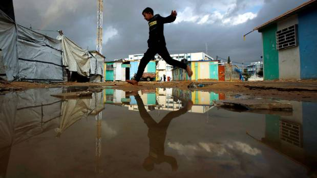 A Palestinian boy, who lives in a container as a temporary replacement for his destroyed house, jumps over a flooded ...