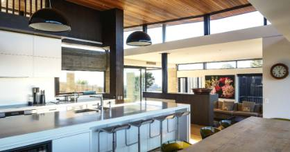 A 4m-long dining table from Indonesia sets the scale for the rest of the room; the large pendant lights help create a ...