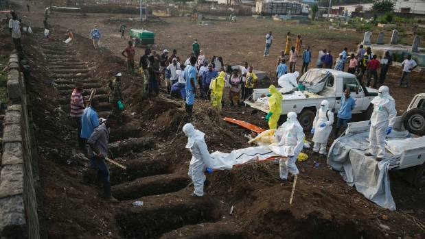 Health workers carry the body of an ebola victim for burial at a cemetery in Sierra Leone during the 2014 West African ...