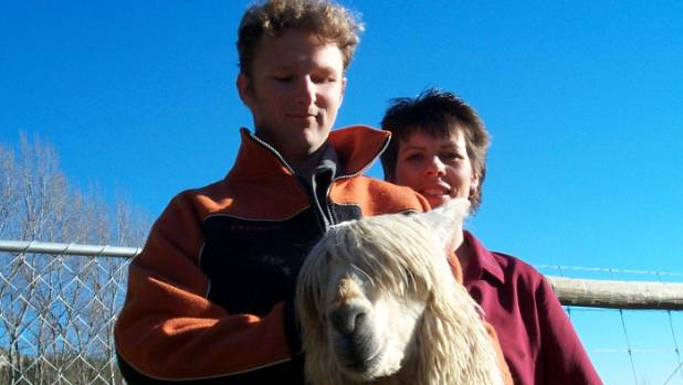 Greg Graham, wife Rachel and one of their alpaca stud animals. The family is waiting to be let back onto their property ...