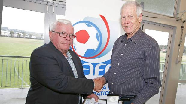 Football historian Barry Smith, right, receives a long service award from Auckland Football Federation's John McLeod.