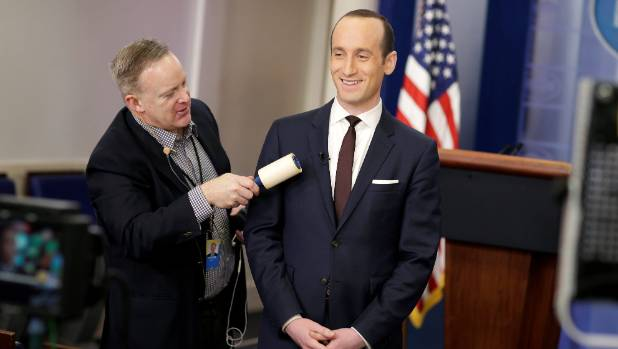 White House Press Secretary Sean Spicer removes lint from Senior White House Advisor Stephen Miller's jacket as he waits ...